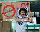 A WWF-India volunteer poses at the photo booth with the message to reuse