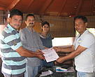 The Livestock Insurance Policy being handed over to one of the beneficiaries by the WWF-India Terai Arc Landscape team and the village head (extreme left) of the Dhela village.